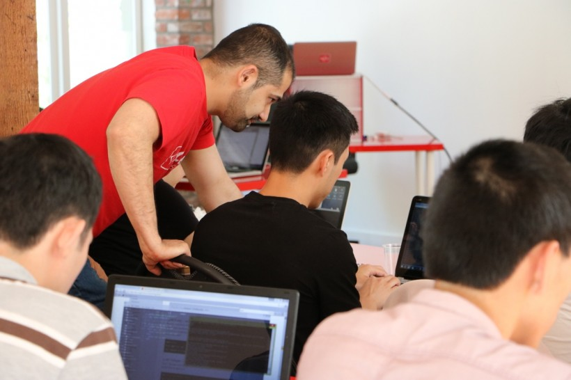 CodeCore owner Tam Kbeili works with students during a classroom session at the Vancouver coding bootcamp.